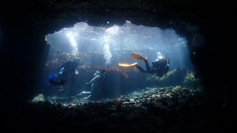 東伊豆、富戸の海の洞窟を中性浮力で泳ぐダイバー
