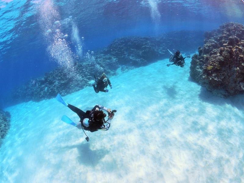 青い海の中で白い砂地の上を中性浮力で泳ぐダイバー